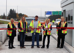 Toll attendants at the Sault Ste. Marie International Bridge are all smiles as they collectively snip the  ceremonial ribbon officially opening the first three new toll lanes for the ongoing toll plaza project. The International  Bridge Administration's goal is to have all six new toll booths serving seven toll lanes completed and usable by the  end of the year.