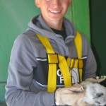 DNR student intern Evan Griffis holds a peregrine falcon chick during banding operations at the Sault Ste. Marie International Bridge June 21. (DNR photo)